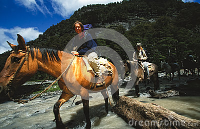 Woman riding horse across river in Patagonia, Agentina Editorial Photography