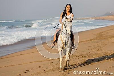 Woman riding horse beach