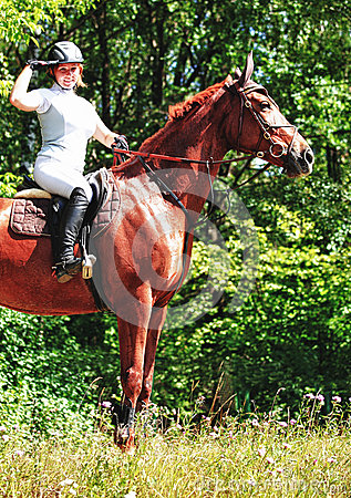 Woman riding horse in country
