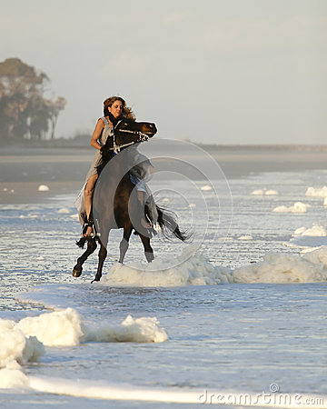 Woman riding wild horse on beach