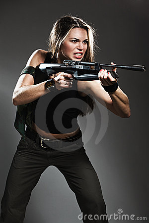 Woman with rifle on dark