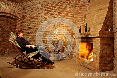 Woman in rocking chair by the fireplace with candl