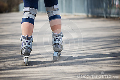 Woman roller skating outdoors Stock Photo
