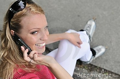 Woman ON rollerblades calling with mobilephone