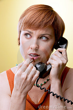 Woman with rotary phone applying lipstick