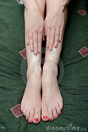 Woman rubbing lotion on legs