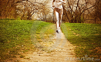 Woman runner in a green forest.
