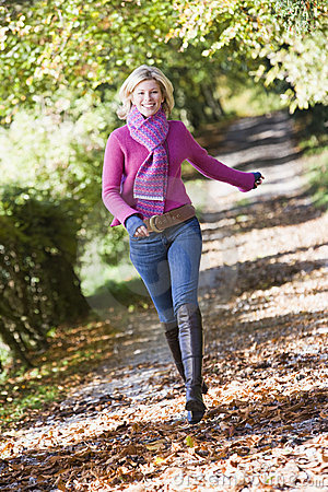 Woman running along autumn path