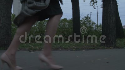 Woman Running Away. Woman is running away in the evening on the street low angle feet view gimbal shot stock video