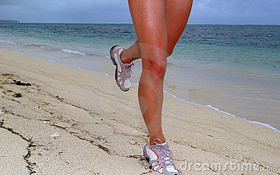 Woman running on beach with sea shoreline background