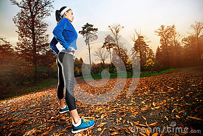 Woman running in the early evening autumn leaves