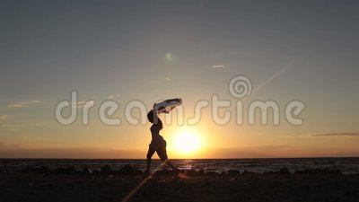 Woman running with flying scarf on beach at sunset stock video footage