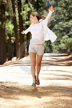 Woman running freely along country path