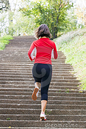 Woman running on park stairs