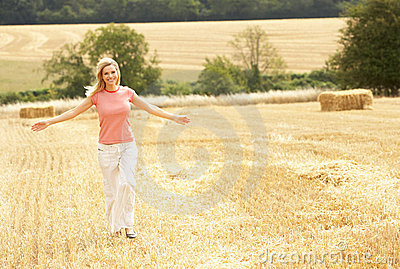 Woman Running Through Summer Harvested Field