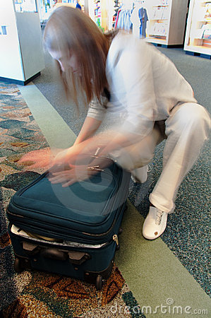 Woman Rushing To Zip Luggage At Airport