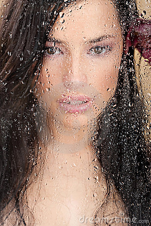 Woman s face behind glass full of water drops