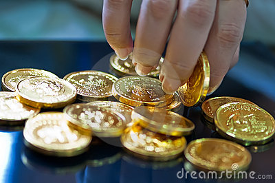 Woman s fingers holding gold coins