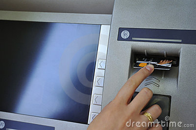 Woman s hand inserting card into cash dispense