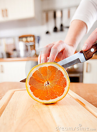 Woman s hands cutting orange
