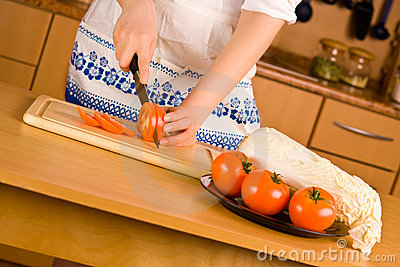 Woman s hands cutting tomato