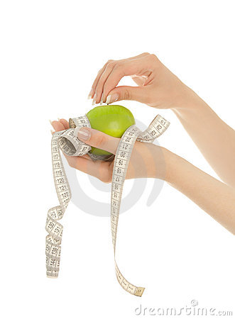 Woman s hands holding apple with measuring tape