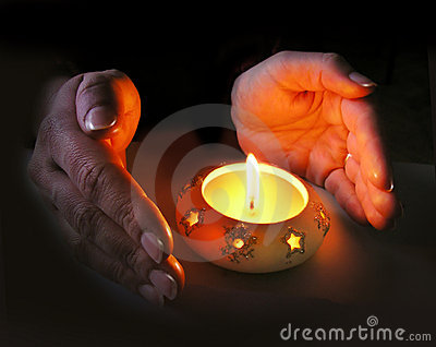 Woman s hands lit by a Christmas candle