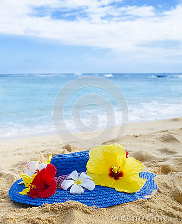 Woman s hat with tropical flowers on sandy beach