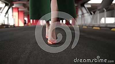 Woman`s legs in high heel shoes walking on road stock video