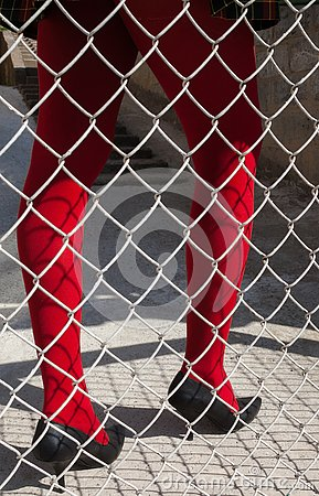 Free Woman`s Legs In Red Tights Behind The Metal Mesh Fence Stock Photography - 149377542