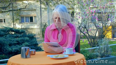 Woman in 70s making a video call outdoor with tablet stock video