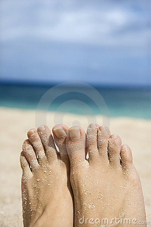 Woman s sandy feet on beach.