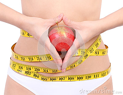 Woman s waist with measuring tape holding apple