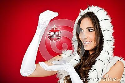 Woman in santa clothes holding shiny xmas ball