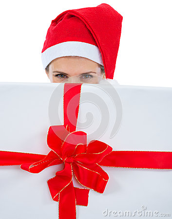 Woman in Santa hat hiding behind Christmas present