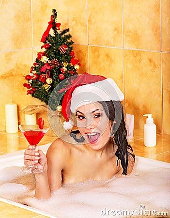 Woman in santa hat relax in bath.
