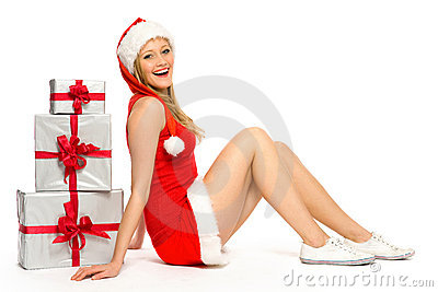 Woman in Santa hat sitting near Christmas presents