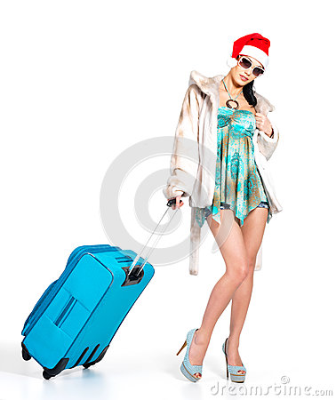 Woman in santa hat  standing with travel suitcase