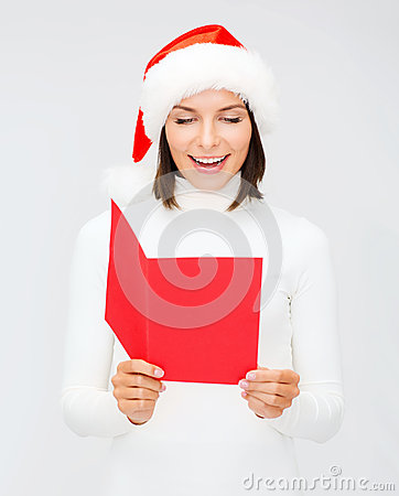 Woman in santa helper hat with blank red postcard