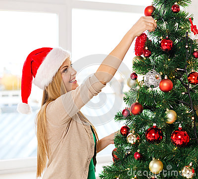 Woman in santa helper hats decorating a tree