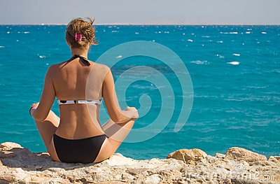 Woman in a sarong meditating on the beach