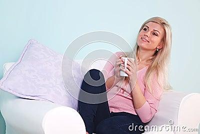 Woman sat in an armchair drinking tea