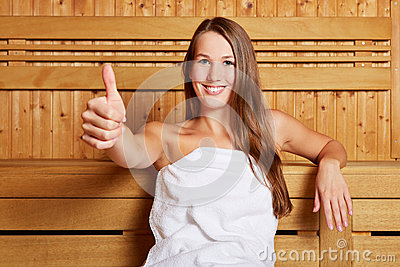 Woman in sauna holding thumbs up