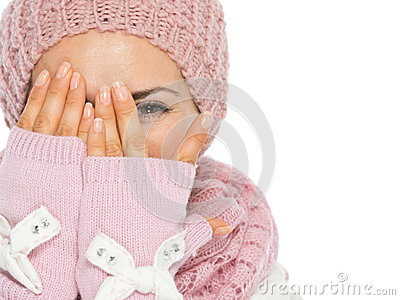Woman in scarf and hat hiding behind hand