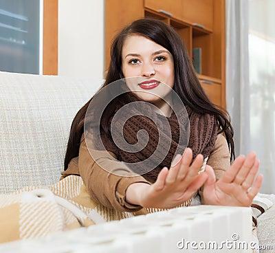 Woman in scarf  warming near warm heater
