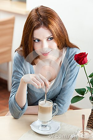 Woman with scarlet rose at the cafe