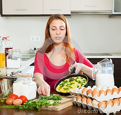 Woman  with  scrambled eggs in pan at home