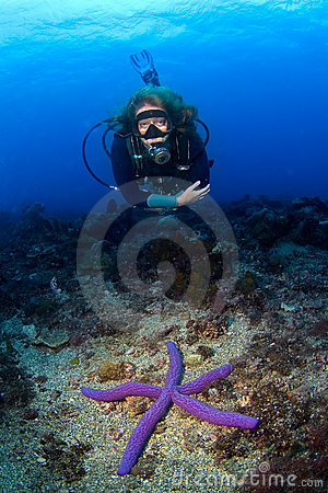Woman scuba-diver swimming over seastar