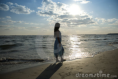 Woman at sea on beach with sun and clouds