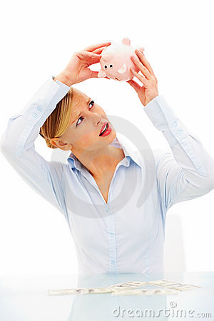 Woman searching cash in empty piggy bank